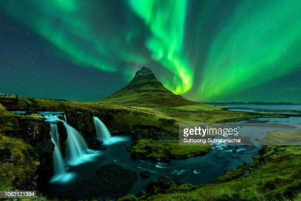 northern lights appear over mount kirkjufell with kirkjufellfoss waterfall in iceland. - islanda foto e immagini stock