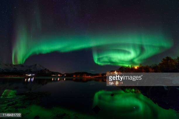 Northern Lights, Aurora Borealis over Northern Norway during winter with reflections in the fjord