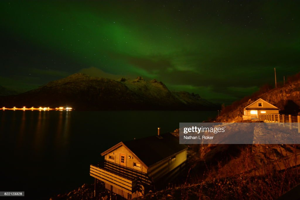 Northern Lights glowing overhead of a rustic cabin retreat. : Stock Photo