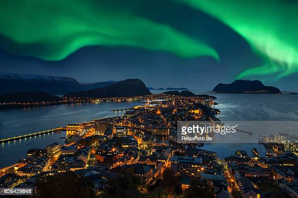 northern lights - green aurora borealis over alesund, norway - norwegen stock-fotos und bilder