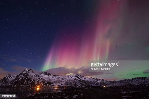 Northern lights illuminate the sky over the snow covered beach of Flakstad on Lofoten Islands Arctic Circle on March 14 2016 Surfers from all over...