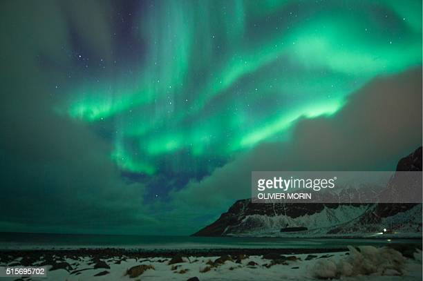 Northern lights illuminated the sky over the snow covered beach of Unstad on Lofoten Island Arctic Circle on March 10 2016 Surfers from all over the...