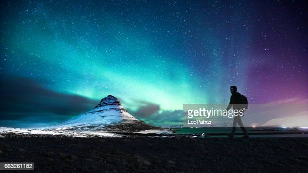 northern lights in mount kirkjufell iceland with a man passing by - impressionante foto e immagini stock