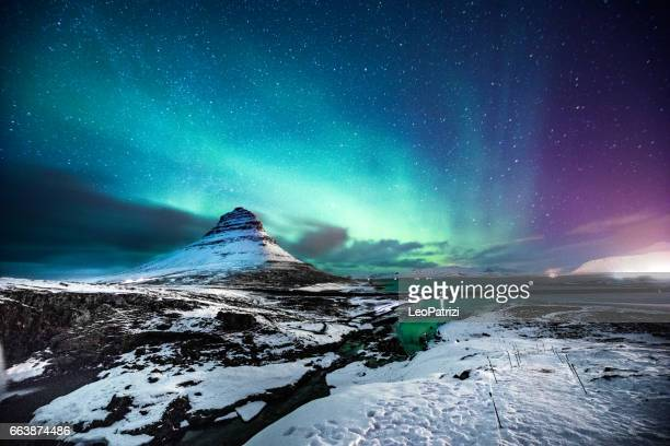 northern lights in mount kirkjufell iceland with a man passing by - islanda foto e immagini stock