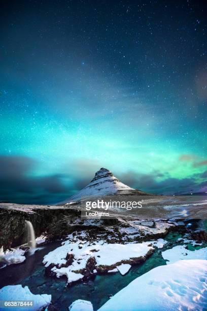 nordlicht in berg kirkjufell island mit einem mann vorbei - norden stock-fotos und bilder
