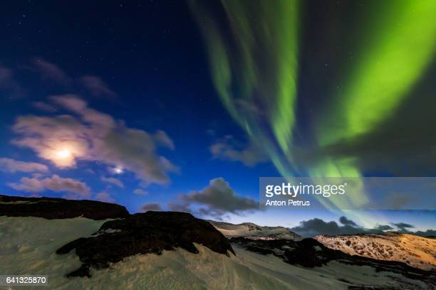 Northern Lights in the mountains and the full moon