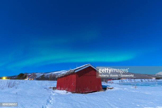 Northern Lights on Lyngen Alps and hut in the snow, Troms, Norway