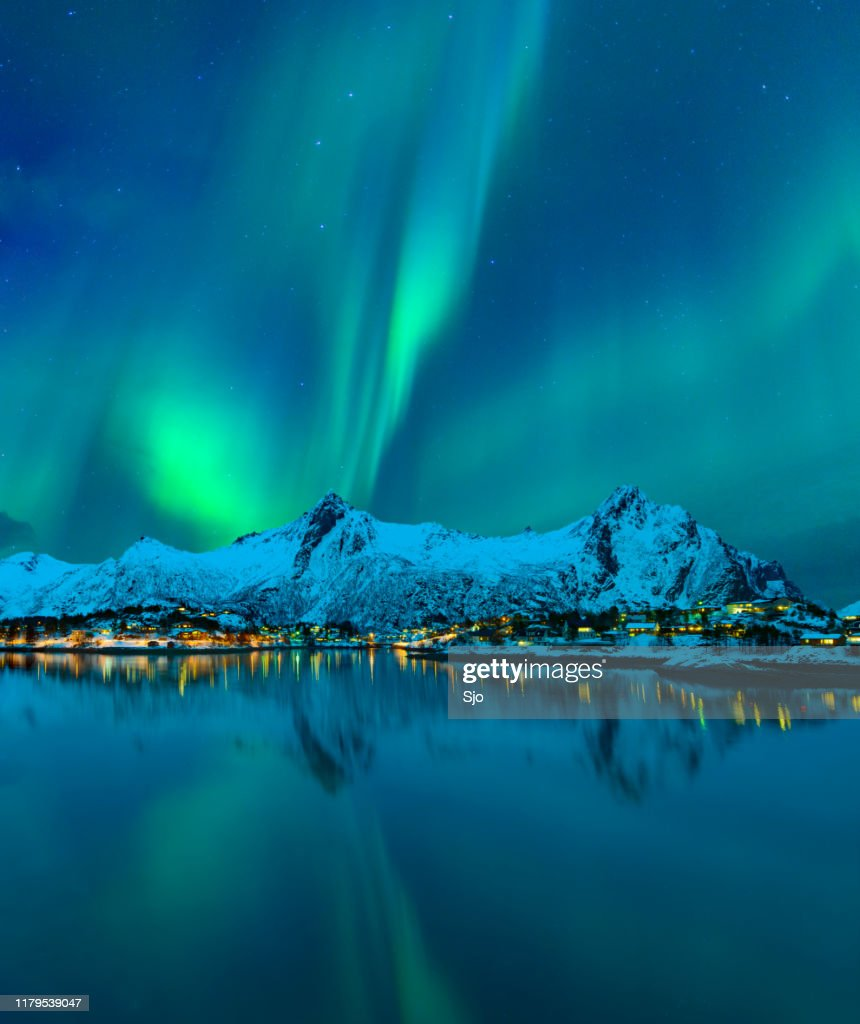 Northern Lights or Aurora Borealis in the night sky over the town of Svolvaer in the Lofoten : Stock Photo