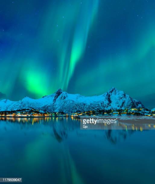 northern lights or aurora borealis in the night sky over the town of svolvaer in the lofoten - norvegia foto e immagini stock