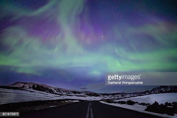 northern lights over distant mountains in iceland - north stock pictures, royalty-free photos & images