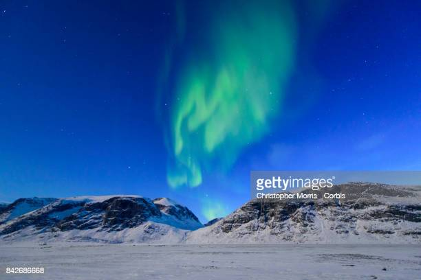 Northern lights over the frozen landscape of Akshayuk Pass, in Auyuittuq National Park on April 8, 2017 on Baffin Island, Canada.