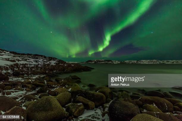 Northern Lights over the rocky coast of the Barents Sea