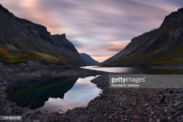 northern nature landscape. mountains, rocks, blurry clouds, mosses and lichens. long exposure shot - eismeer stock-fotos und bilder