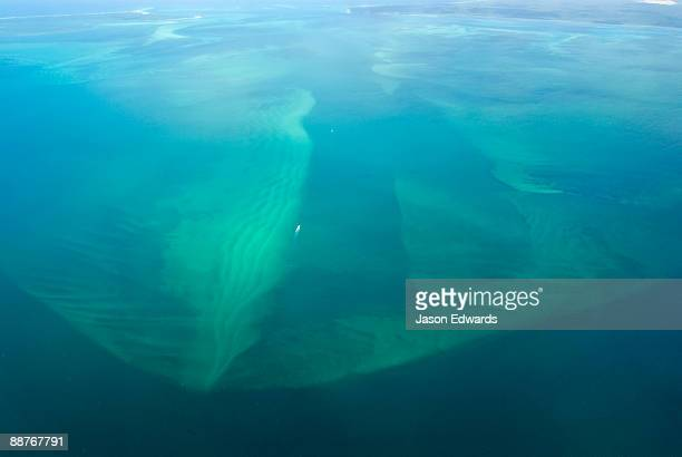 A boat is dwarfed by a massive sand bar off the Queensland coastline.