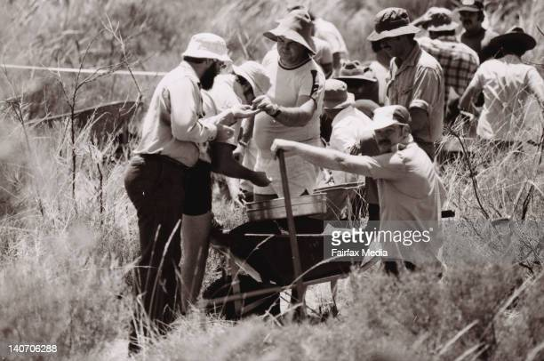 Northern Territory pathologists and CSIRO technicians examine samples around Ayers Rock where baby Azaria Chamberlain disappeared two years earlier...