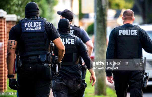 MANASSAS VA Northern Virginia Gang Task Force officers partnering with ICE officers walk in force toward a house to arrest an MS13 gang member in...