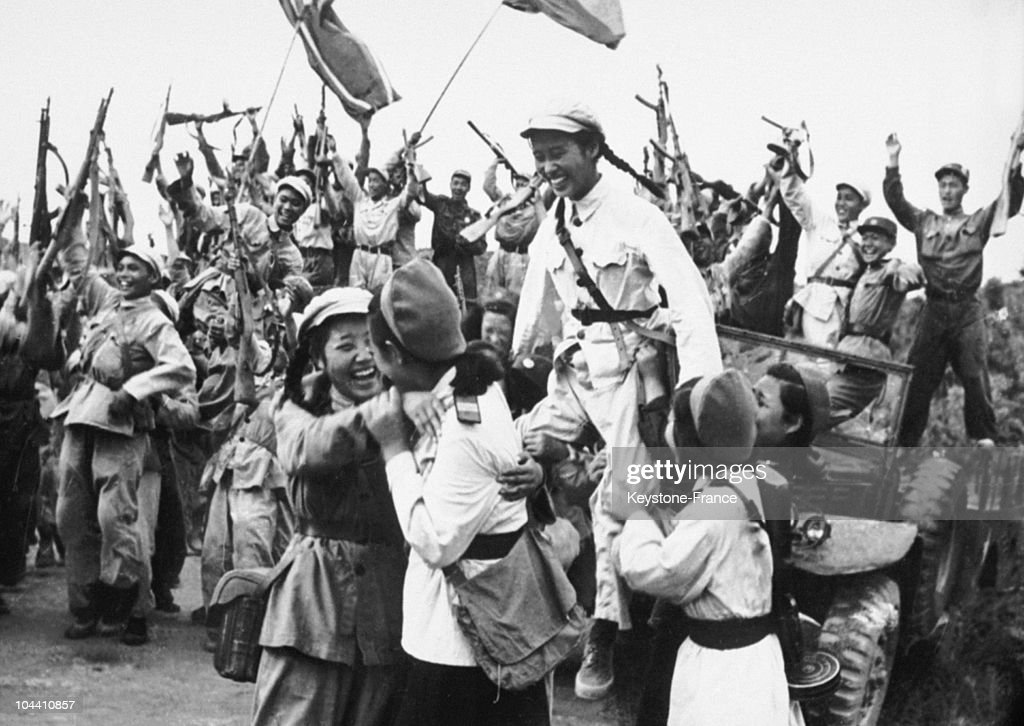North-Korean and Chinese troops celebrate their shared victory in South Korea after having driven back an attack of American forces in June 1950. In the foreground, women soldiers express their joy. This scene took place around June 25, 1950, when North Korea crossed the 38th parallel and invaded South Korea.