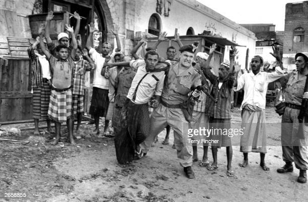 A Northumberland Fusilier imposes law and order on Arab demonstrators during a disturbance in the Crater district of Aden
