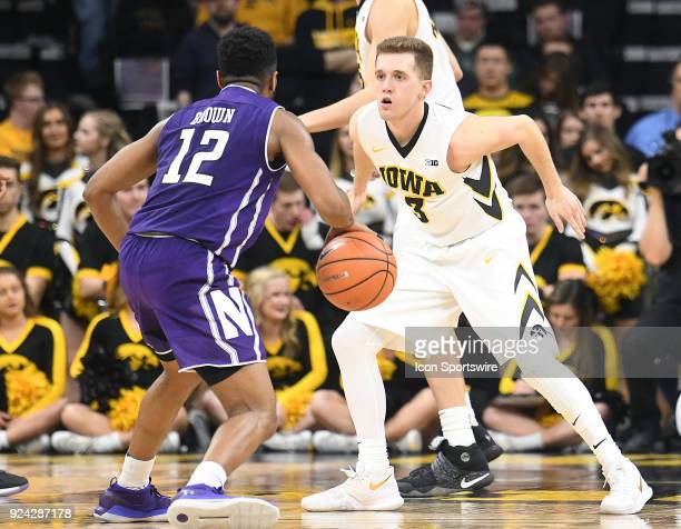 Northwestern guard Isiah Brown tries to drive past Iowa guard Jordan Bohannon during a Big Ten Conference basketball game between the Northwestern...