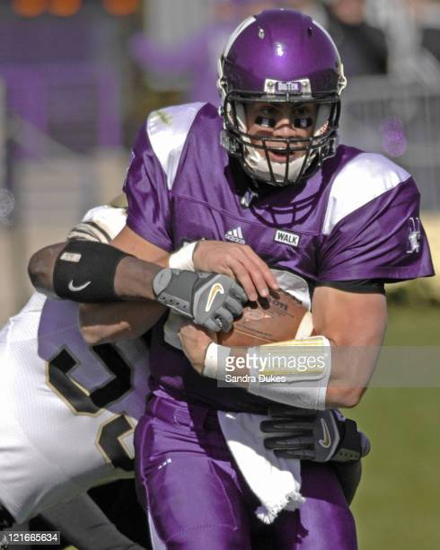 Northwestern QB Andrew Brewer brings a Purdue linebacker with him as he runs up field in a game won by Purdue over Northwestern 31-10 at Ryan Field...