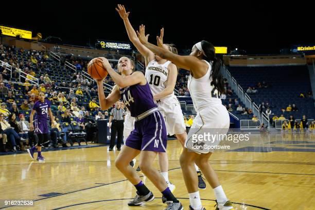 Northwestern Wildcats forward Abi Scheid shoots over Michigan Wolverines guard Nicole Munger and Michigan Wolverines guard Deja Church during a...
