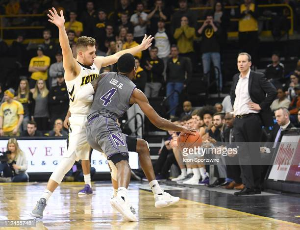 Northwestern Wildcats forward Vic Law passes the ball around Iowa Hawkeyes guard Jordan Bohannon during a Big Ten Conference basketball game between...