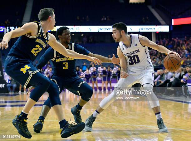 Northwestern Wildcats guard Bryant McIntosh handles the basketball in front of Michigan Wolverines guard Duncan Robinson and Michigan Wolverines...