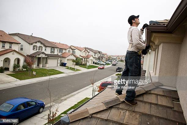 NorthWoods inspector Manny Nevarez inspects the roof of a foreclosed home for needed repairs December 2 2008 in Sacramento California Many foreclosed...