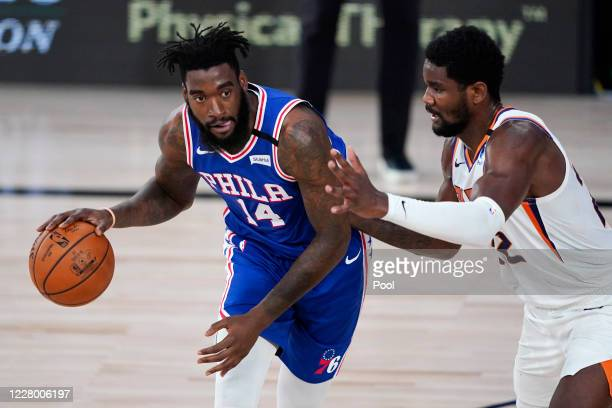 Norvel Pelle of the Philadelphia 76ers handles the ball against Deandre Ayton of the Phoenix Suns during the first half of a NBA basketball game at...