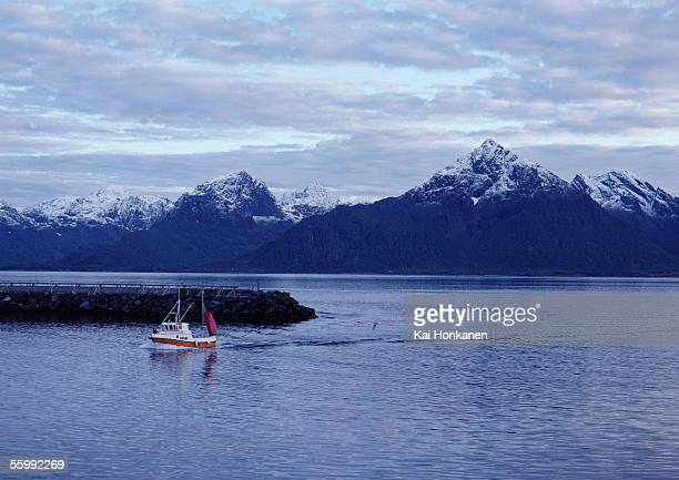 Norway, fishing boat close to jetty, snow-capped mountains in background