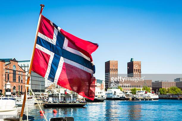 norway flag in front of oslo city hall and marina - norwegian flag stock pictures, royalty-free photos & images