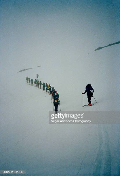 norway, group of randonee skiers moving in single file - medium group of people stock pictures, royalty-free photos & images