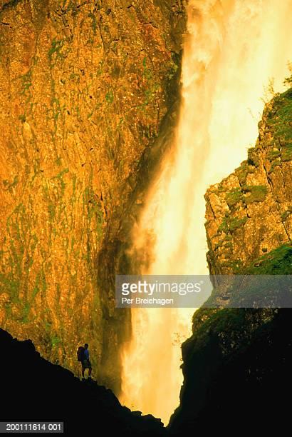 Norway, Hardanger, Voringsfossen, man standing by waterfall