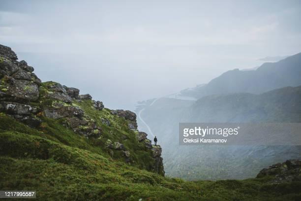 norway, lofoten islands, reine, man looking at view fromreinebringenmountain during rain - northern norway stock pictures, royalty-free photos & images