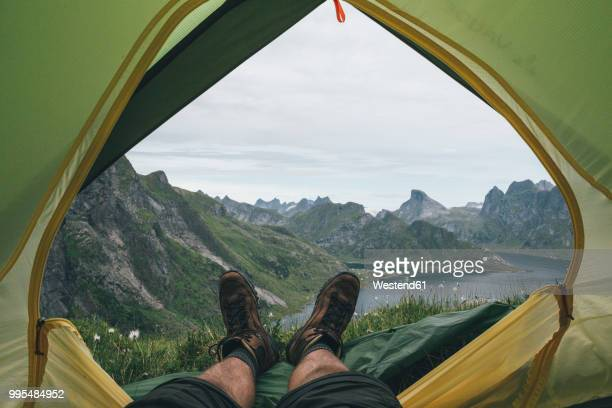 norway, lofoten, moskenesoy, feet of man, lying in a tent over kjerkefjord - hiking boots stock photos and pictures