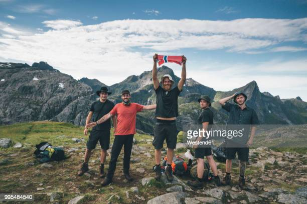 norway, lofoten, moskenesoy, group of young men cheering with norwegian flag - norwegian flag stock pictures, royalty-free photos & images