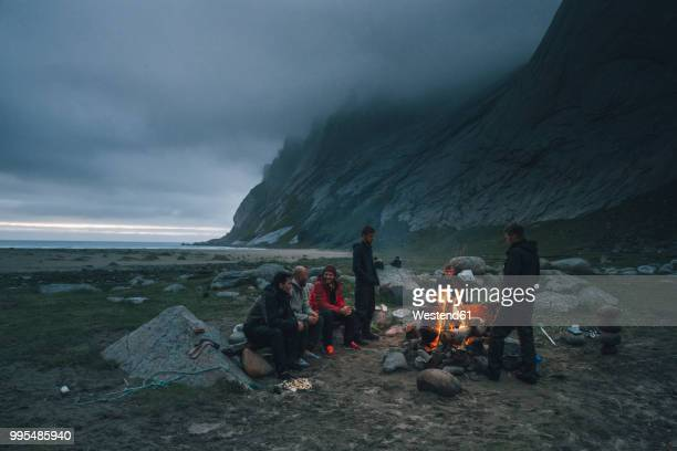 norway, lofoten, moskenesoy, group of young men sitting at a campfire at bunes beach - lagerfeuer stock-fotos und bilder