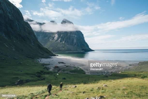 norway, lofoten, moskenesoy, young men hiking at kvalvika beach - lofoten stock pictures, royalty-free photos & images