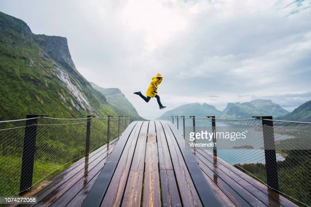 norway, senja island, man jumping on an observation deck at the coast - high up stock pictures, royalty-free photos & images