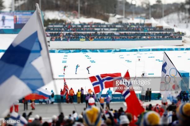 TOPSHOT Norway supporters wave the flag as Norway's Martin Johnsrud Sundby Italy's Francesco De Fabiani and France's Maurice Manificat compete during...