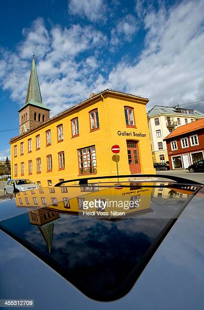 Norway; The bell tower of Kampen church and the yellow fasade of Bastian Gallery reflected in the roof top of a parked car in Bøgata, Oslo.
