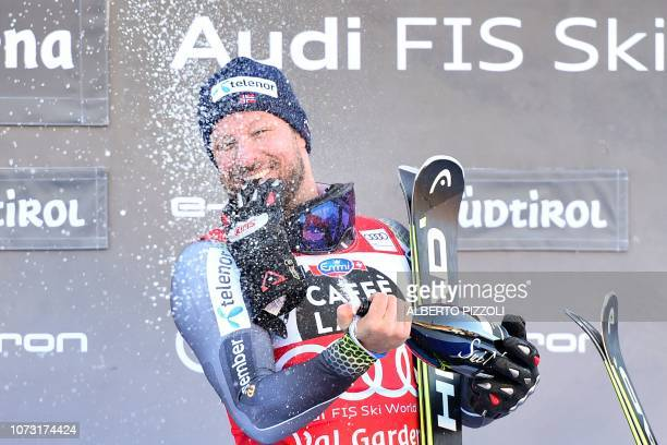 Norway's Aksel Lund Svindal sprays champagne as he celebrates on the podium after winning the FIS Alpine World Cup Men Super G on December 14 2018 in...