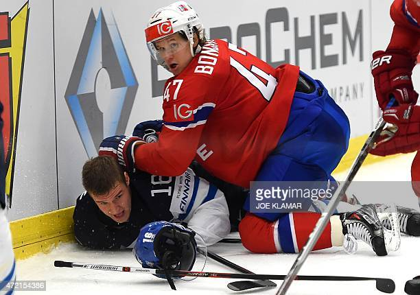 Norway's Aleksander Bonsaksen holds down Finland's Aleksander Barkov during the group B preliminary round ice hockey match Norway vs Finland of the...