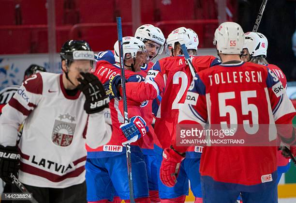 Norway's Andreas Martinsen celebrates with his teammates as he scores a goal during a preliminary round match against Latvia at the Ice Hockey World...
