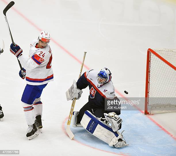 Norway's Andreas Martinsen watches the puck flying past Slovakia's goalkeeper Jan Laco during the group B preliminary round match Slovakia vs Norway...