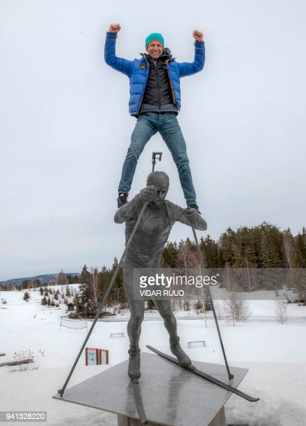 Norway's biathlon superstar Ole Einar Bjoerndalen climbs on the top of the statue of himself after a press conference where he announced his...