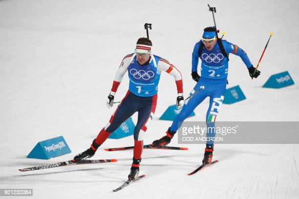 Norway's Emil Hegle Svendsen and Italy's Dominik Windisch race to the finish line to win silver and bronze in the mixed relay biathlon event during...
