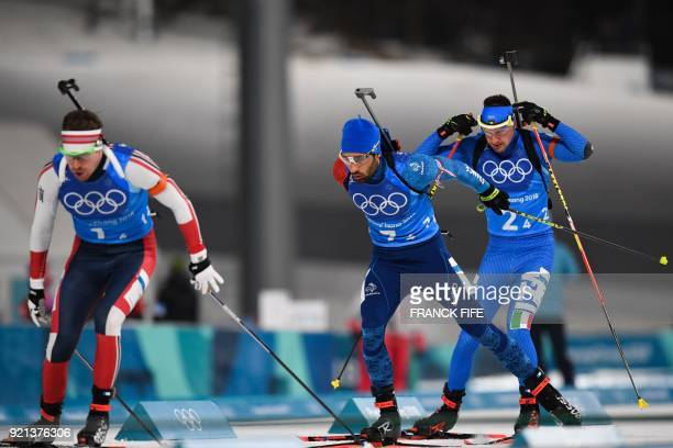 Norway's Emil Hegle Svendsen France's Martin Fourcade and Italy's Dominik Windisch compete in the mixed relay biathlon event during the Pyeongchang...