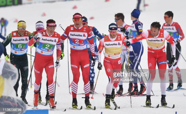 Norway's Emil Iversen exchanges with Norway's Martin Johnsrud Sundby as Russia's Andrey Larkov exchanges with Russia's Alexander Bessmertnykh during...