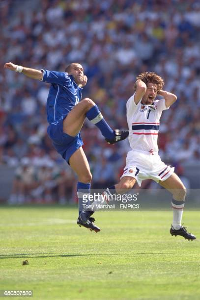 Norway's Erik Mykland holds his head as he and Italy's Luigi Di Biagio go up for a high ball